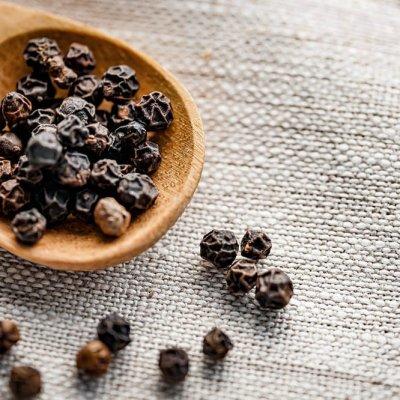 Cuchara con granos de pimienta negra