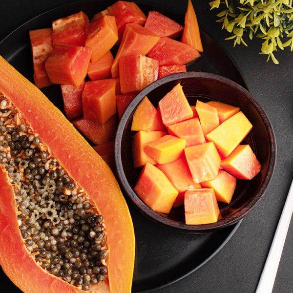 Mesa con papaya cortada en cuadrados